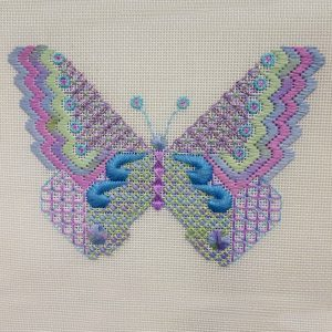Colourful butterfly embroidered on canvas with lots of textured stitches