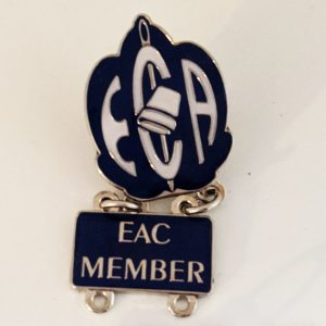 "Enamel pin with the EAC shield logo and a second pin below with ""EAC Member"" text"