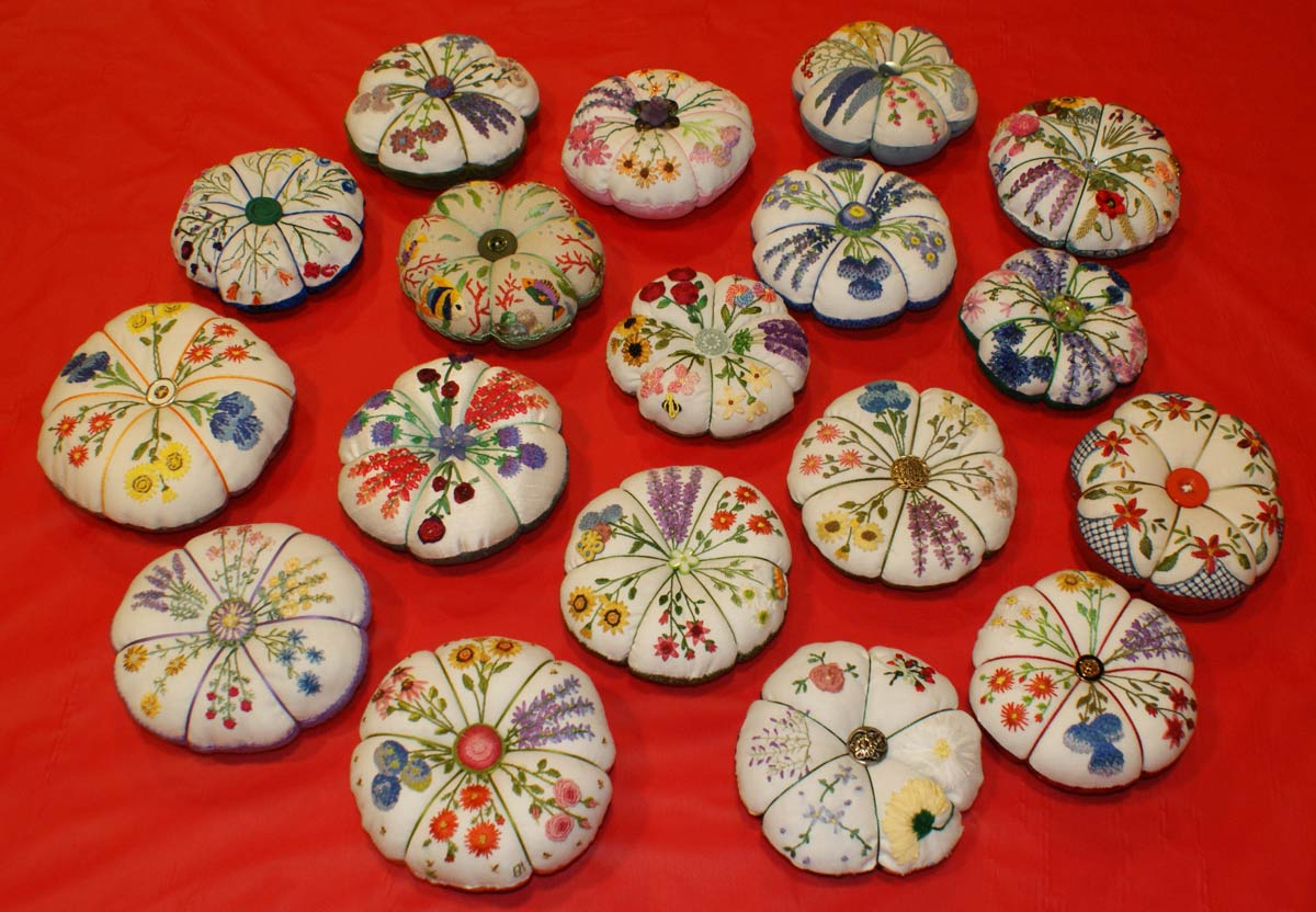 Group of small pin cushions that are embroidered with various flowers