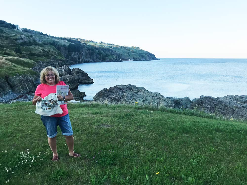 Photo of a woman on a grassy area with a rocky shoreline and water in the background. The owman is holding a magazine and some embroidery.