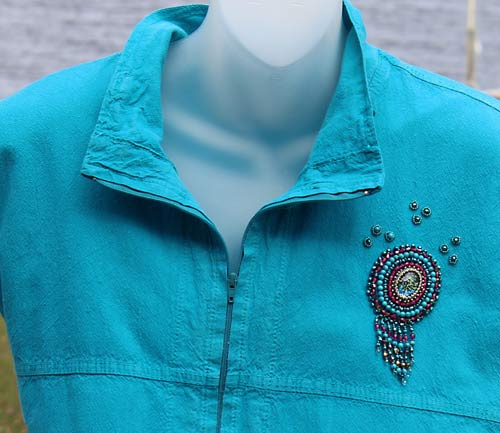 photo of a blue top with w beaded design on the shoulder