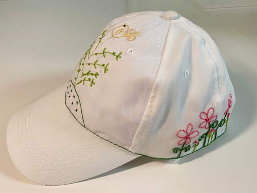 photo of a baseball style cap with embroidered flowers on it