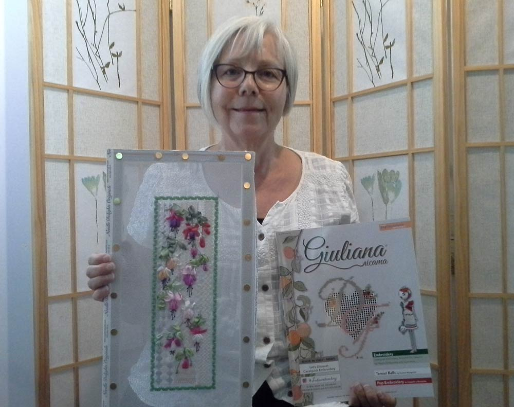 Photo of a woman holding a copy of the Giuliana Ricama magazine and a piece of canvas work enbroidery with colourful fuchsia flowers stitched with silk ribbon