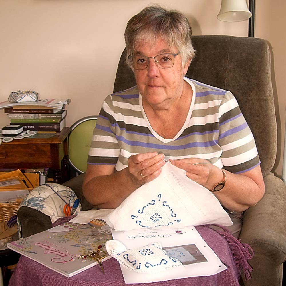 photo a woman in a comfortable chair embroidering a blue design on a white piece of fabric