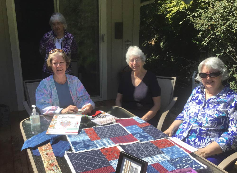 photo of a group of four women outside with embroidery on the table in front of them and a copy of Giuliana Ricama magazine.