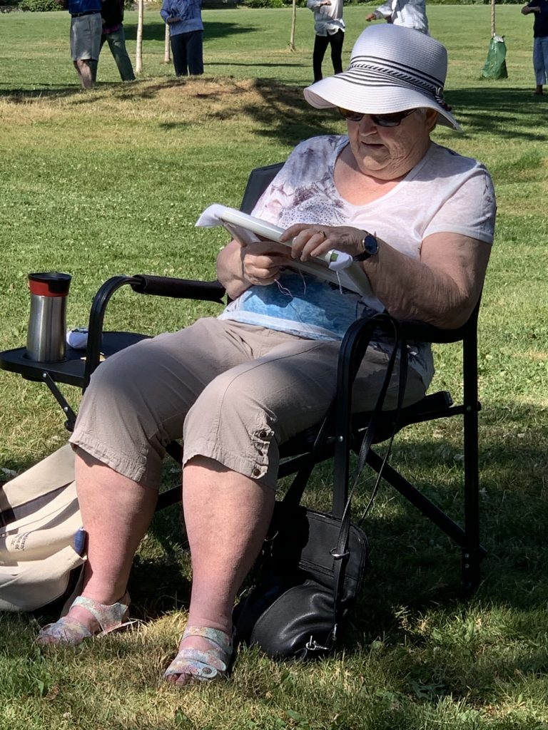 photo of a woman in a lawn chair doing embroidery outside in the shade
