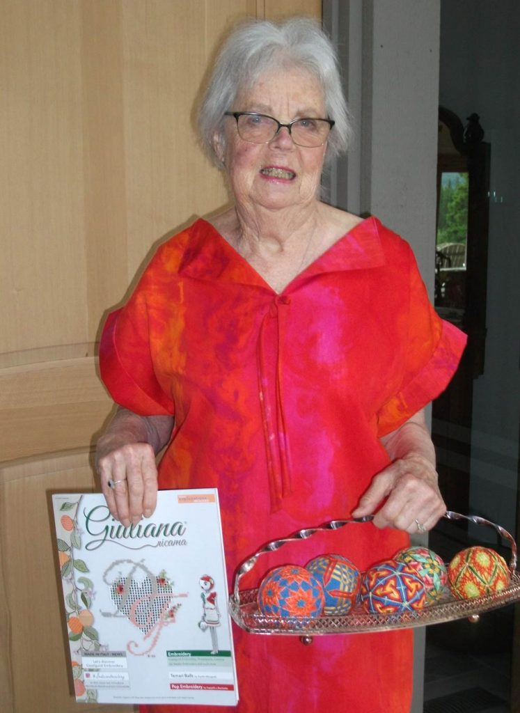 photo of a woman in a bright red dress holding a copy of Giuliana Ricama magazine and a basket with five temari - balls with surface patterns made with thread.