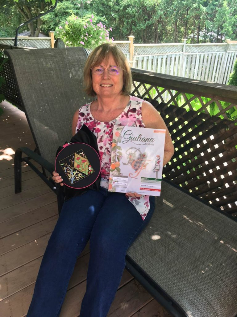 phot of a woman sitting on a outdoor deack holding a piece of embroidery and Giuliana Ricama magazine.