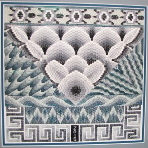 Canvas work style of embroidery in grey threads with Roman key and turtle shaped borders, diamond, zigzag and clamshell shapes in the middle.