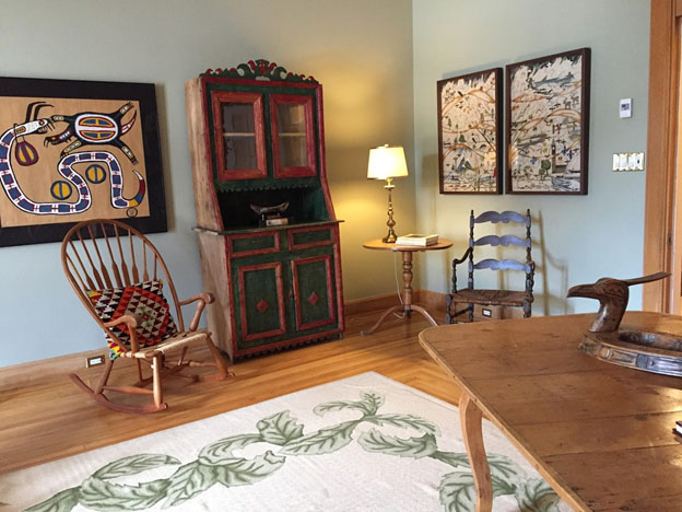 a photograph of a room with some antique furniture, art objects and the Canadian Embroidery Tapestry hung on the wall